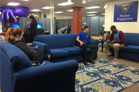 "Students take some time to relax between classes in the new ""living room"" on campus - the Office of Student Engagement."